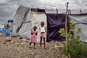 Children stand in front of their shelter at a camp for people displaced by an earthquake, Haiti © UN Photo/Logan Abassi